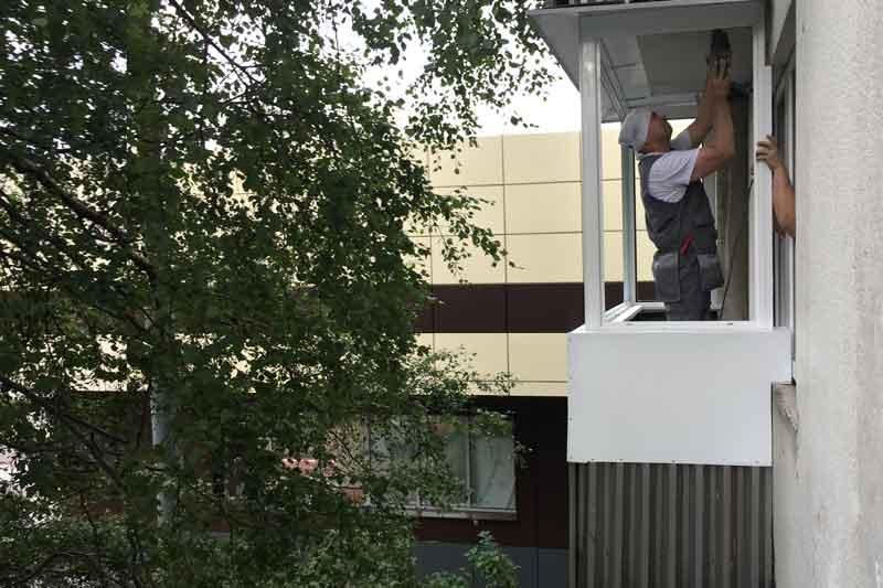 Монтажники устанавливают алюминиевые окна