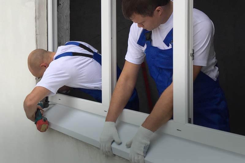 Монтажники устанавливают раму ПВХ окна